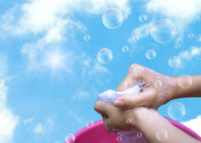 Female Hand washing clothes in the pink basin with clear Bubble. Soap against blue sky and sunlight Royalty Free Stock Image