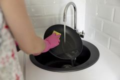 Female hand washing frying pan under running water. Young housewife woman washing griddle in a kitchen sink with a yellow. Sponge, Hand cleaning, manually, by stock photography