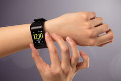 Female hand wearing and pressing smartwatch Stock Photography