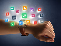 Female hand wearing smartwatch with app icons Stock Image