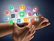 Female hand wearing smartwatch with app icons Stock Photos