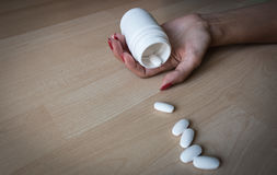 Female hand with white bank, pills on a wooden background Stock Image