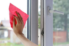 Female hand wiping the glass. Washes white plastic window. Close Stock Images