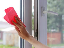 Female hand wiping the glass. Washes white plastic window. Close Royalty Free Stock Photo