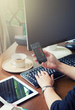 Female hand working computer on working wooden desk with coffee and mobile phone and soft focus, flare sun light, cr Royalty Free Stock Images