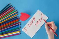 Female hand write love you words in notebook Stock Photos