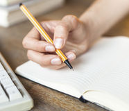 Female hand writes in a notebook diary. Work. Royalty Free Stock Image