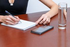 Female hand writes a pen in a notebook, on the Desk next to a smartphone and a glass of water stock images