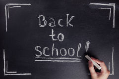 Female hand writes the phrase Back to school with white chalk on black chalkboard. Royalty Free Stock Photography