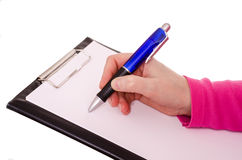 Female hand is writing with a ballpen. On a white paper sheet Royalty Free Stock Images