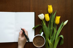 Female hand writing in a book. Next to a cup of coffee and tulips on a wooden table Royalty Free Stock Photo