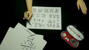 Female hand writing chinese calligraphy using brush and ink on rice paper. Close up on hand holding brush while writing Stock Images