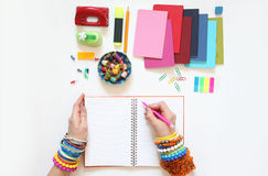 Female hand writing in diary. Colored bracelets, scarf, turtlene Royalty Free Stock Image