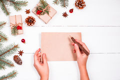 Female hand writing a letter to Santa on holiday background with Christmas gifts, Fir branches, pine cones, red decorations. Xmas Royalty Free Stock Photography