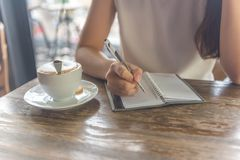 Female hand writing note beside cup of hot cappuccino stock photos