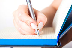 Female hand writing in a notebook Stock Photography