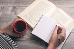 Female hand writing on a notebook on the floor. With a cup of coffee and a book Stock Photography