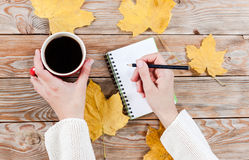 Female hand writing in notebook near cup of coffee Royalty Free Stock Photo