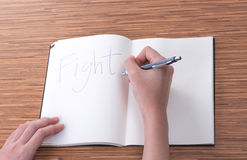 Female hand writing in notebook on table. Female hand writing in notebook Stock Image
