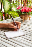 Female hand writing in a notebook on wooden table Stock Photo