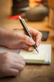 Female hand writing on notepad Stock Photo