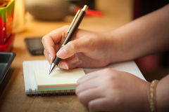 Female hand writing on notepad Stock Images