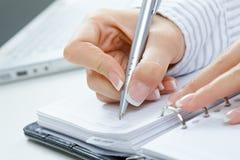 Female hand writing notes Royalty Free Stock Image