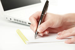 Female hand writing notes on the notepad Stock Photos