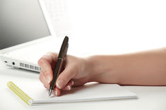 Female hand writing notes on the notepad Stock Images