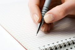 Female hand writing on page. Royalty Free Stock Photos