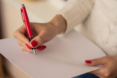 Female hand writing on a sheet of paper. Female hands with red nails write on a sheet of paper Stock Photos