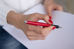Female hand writing on a sheet of paper. Female hands with red nails write on a sheet of paper Stock Photo