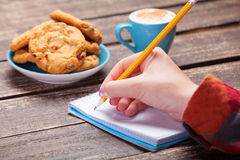 Female hand writing something. In note near cookie and cup of coffee Stock Photography