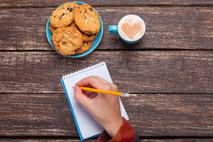 Female hand writing something in note. Near cookie and cup of coffee Stock Images