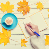 Female hand writing something in notebook near cup of coffee. Stock Photography