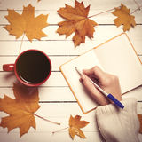 Female hand writing something in notebook near cup of coffee. Royalty Free Stock Photos