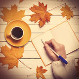 Female hand writing something in notebook near cup of coffee. Royalty Free Stock Photo