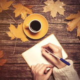 Female hand writing something in notebook near cup of coffee. Royalty Free Stock Image
