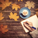 Female hand writing something in notebook near cup of coffee. Royalty Free Stock Images