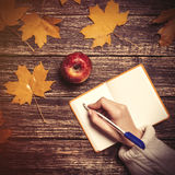 Female hand writing something in notebook next to apple Royalty Free Stock Images