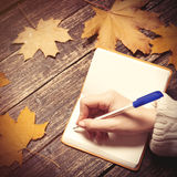 Female hand writing something in to note Royalty Free Stock Photo