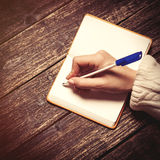 Female hand writing something in to note Stock Image
