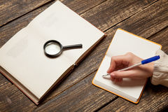Female hand writing something. In to notebook Stock Photo