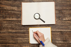Female hand writing something. In to notebook Royalty Free Stock Photos