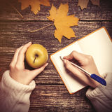 Female hand writing something in to notebook and holding apple Stock Photo