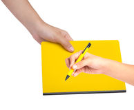 Female hand writing on a yellow book Royalty Free Stock Photos