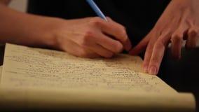 Female hand writing yellow notebook