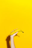 Female hand on a yellow background holds a fresh banana. Banana in hand on a yellow background with a shadow Stock Image