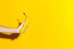 Female hand on a yellow background holds a fresh banana Stock Photo
