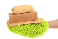 Female hand with a yellow chamois and sponge mitt Stock Photos